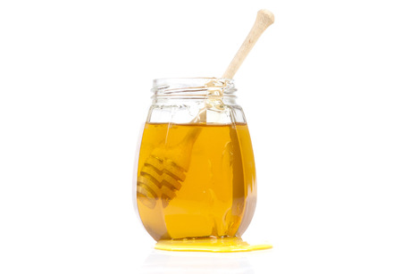 drizzler: Glass jar of honey with wooden drizzler on a white background.