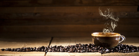 Glass coffee cup and coffee beans on old wooden background.