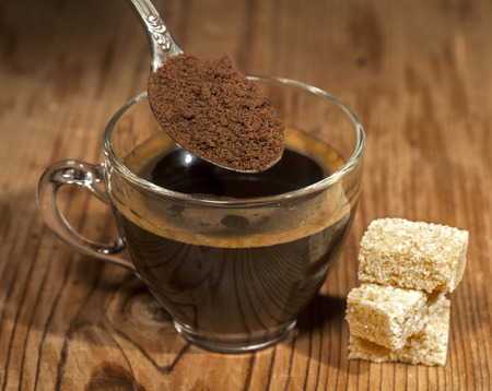 Glass coffee cup and spoon with instant granulated coffee on old wooden background.
