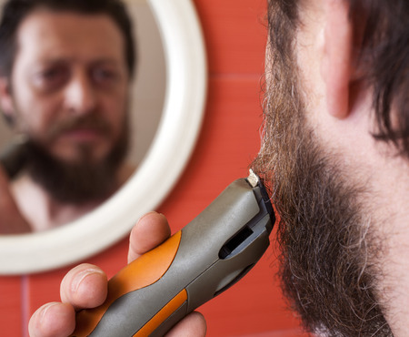 electric shaver: Bearded man trim his beard with electric shaver. Stock Photo