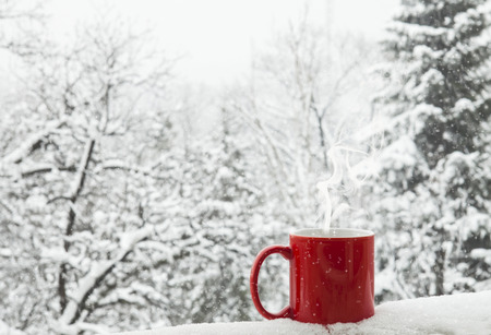 Red cup of coffee on a beautiful snow winter background. photo
