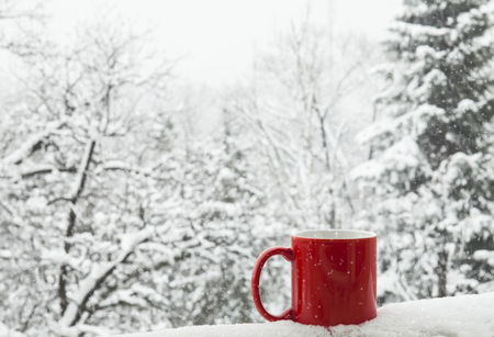 Red cup of coffee on a beautiful snow winter background.