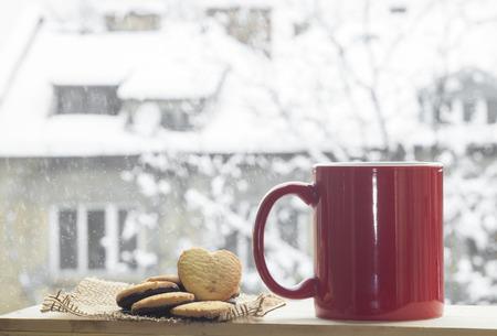 아름다운 눈이 겨울 배경에 커피 레드 컵.