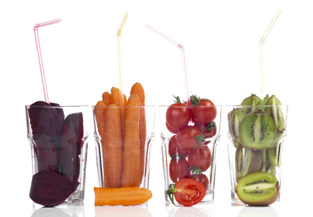 fresh fruits and vegetables in glass cups on a white background. Banque d'images