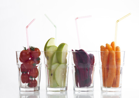 fresh fruits and vegetables in glass cups on a white background. photo