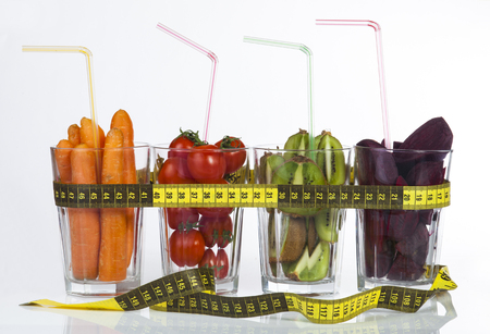 fresh fruits and vegetables in glass cups with measuring tape on a white background. photo