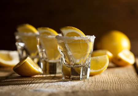 cocktail drinks: Three tequila shots with lemon and salt on wooden background.