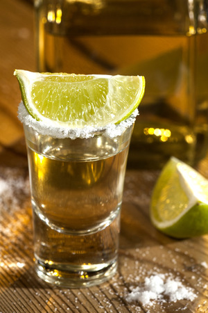 Gold tequila shot with lime fruits on wooden background photo