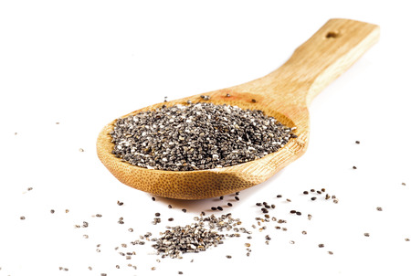 brown white: Chia seeds in wooden spoon isolated on white background. Stock Photo