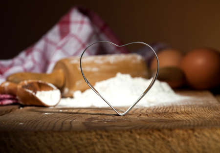 cookie cutter: Kitchen utensils with flour and cookie cutter on wooden background.
