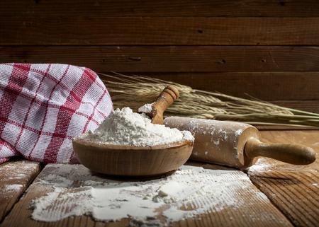 Flour and kitchen utensils on wooden background.