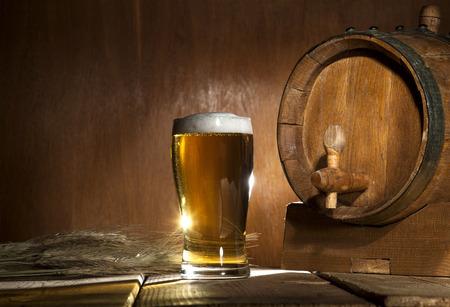 beer foam: Beer barrel with beer mug on a wooden dark background.