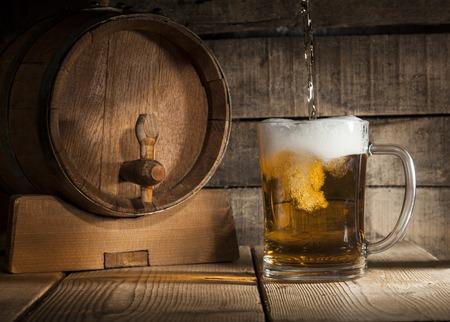 grifos: Barril de cerveza con jarra de cerveza sobre un fondo oscuro de madera. Foto de archivo