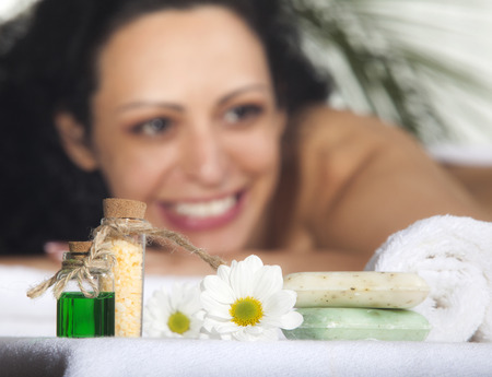 exfoliate: Beautiful Woman Getting Spa Massage in Spa Salon. Focus on the flower.