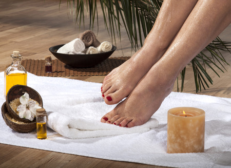 Female feet with drops of water on spa background.