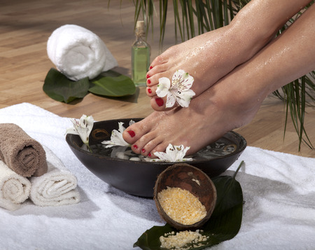 footcare: Female feet with drops of water soaked in spa bowl with flowers and rocks.