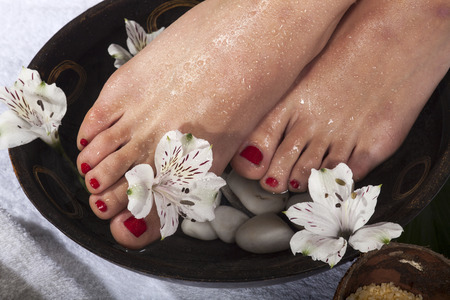 easing: Female feet with drops of water soaked in spa bowl with flowers and rocks.