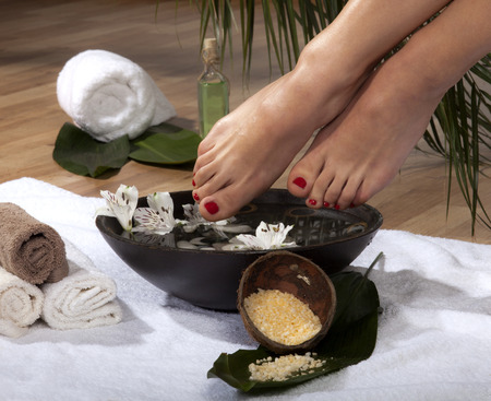 Female feet soaked in spa bowl with flowers and rocks.