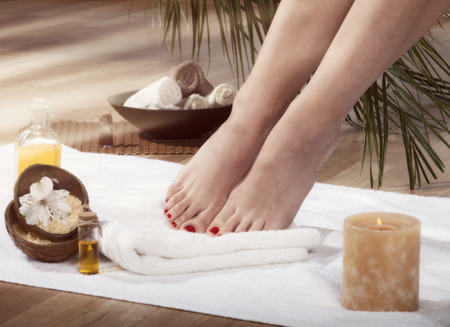 Female feet with drops of water on spa background. With special lighting effect. photo