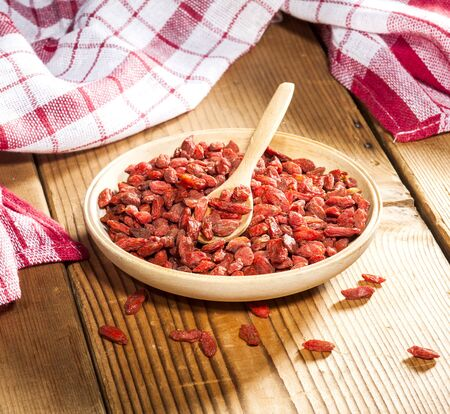tibet bowls: Wooden bowl with goji berries on wooden background.