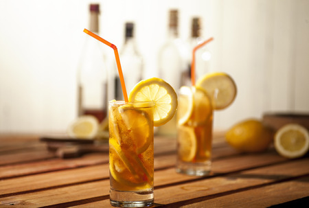 long: Long island ice tea coctails on wooden and white background.