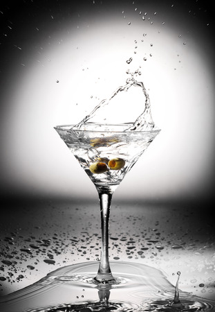 Glass of martini cocktail with olives and splashes