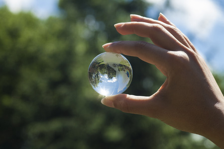 World environmental concept. Crystal globe in human hand on beautiful green and blue bokeh. Visible are the continents the Americas Standard-Bild