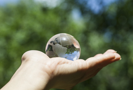 transparent globe: World environmental concept. Crystal globe in human hand on beautiful green and blue bokeh. Visible are the continents the Americas Stock Photo