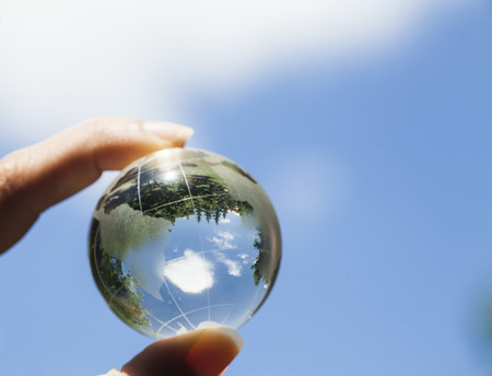 World environmental concept. Crystal globe in human hand on a blue sky background. Visible are the continents the Americas Standard-Bild