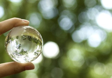 business environment: World environmental concept. Crystal globe in human hand on beautiful green bokeh. Visible are the continents the Americas