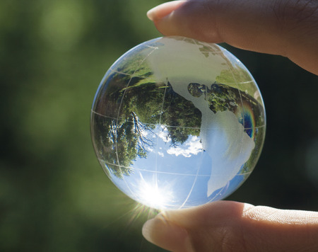 plant life: World environmental concept. Crystal globe in human hand on beautiful green and blue bokeh. Visible are the continents the Americas Stock Photo