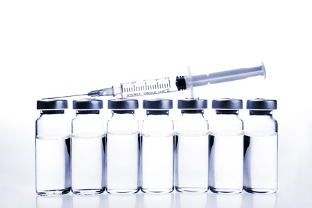 tinted: Glass Medicine Vials and hualuronic collagen or flu syringe. Tinted image. Stock Photo