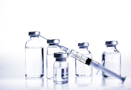Glass Medicine Vials and hualuronic collagen or flu syringe. Tinted image. Reklamní fotografie