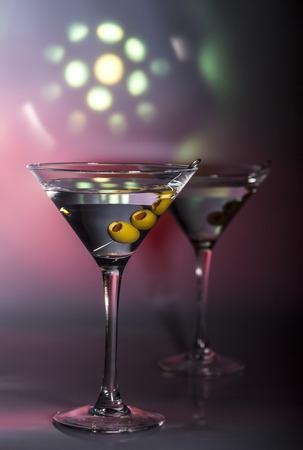 copa martini: Dos vasos de c�ctel de martini con aceitunas verdes sobre un fondo color mezclado.