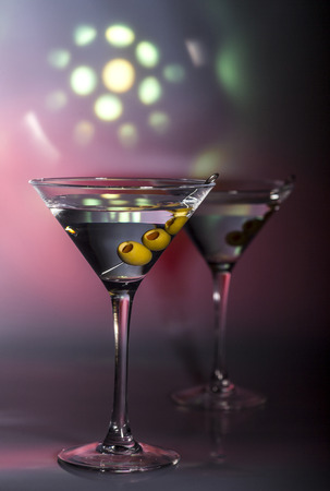martini: Two glasses of martini cocktail with green olives on a mixed color background.