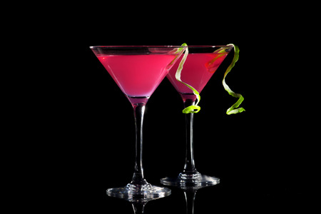 martini: Two glasses of cosmopolitan coctail on a black background. Stock Photo