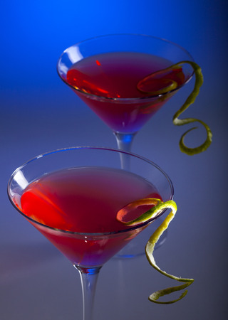 cosmopolitan: Two glasses of cosmopolitan coctail on a blue background.