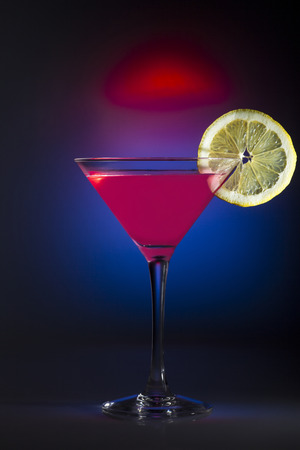 colores: Glass of cosmopolitan coctail on a mixed colores background.