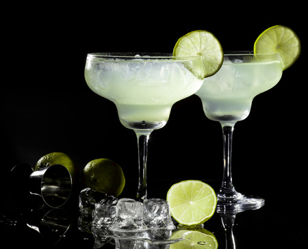 Two glasses of margarita cocktail on a black background. 스톡 콘텐츠