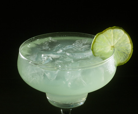 bartending: Glass of margarita cocktail on a black background. Stock Photo