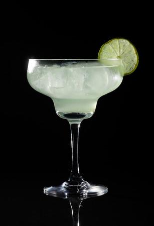 Glass of margarita cocktail on a black background. Standard-Bild