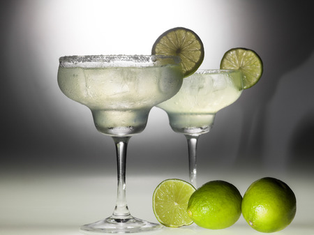 Two glasses of margarita coctail on black and white background with deep shadows.
