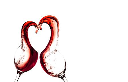 흰색 배경에 추상 심장 스플래시와 레드 와인 두 잔