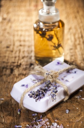 exfoliate: Spa background with bar soap, bunch of lavender and bottle with aromatherapy oil on a wooden background. Stock Photo