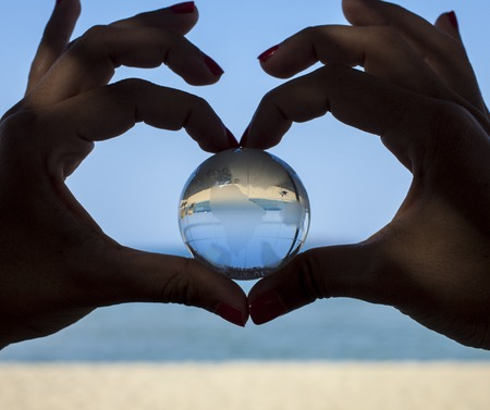 peace concept: Environmental concept - close up of human hands showing heart shape gesture and holding crystal globe.