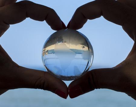 Concepto de medio ambiente - cerca de las manos del hombre que muestra la forma del corazón el gesto y la celebración de globo de cristal.