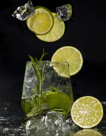 alcoholic drink: Glass with alcoholic drink with lime and ice on a black background.