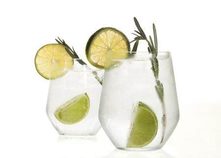 coctel de frutas: Vidrio con la bebida alcohólica con limón y hielo aislados sobre fondo blanco. Foto de archivo