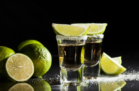 Gold tequila shots with lime fruits isolated on white background