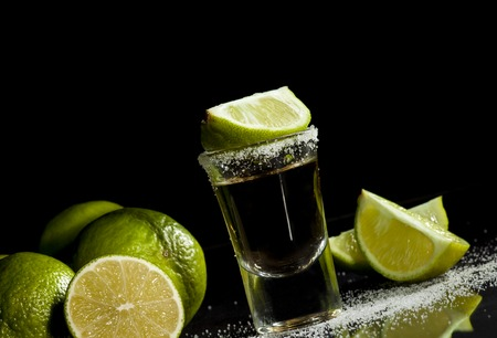 Gold tequila shot with lime fruits isolated on white background